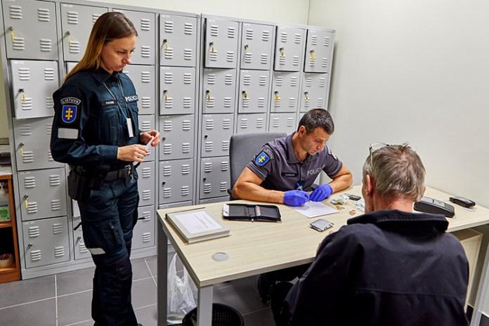 Człowiek siedzi na komisariacie na Litwie, policja spisuje protokół.
