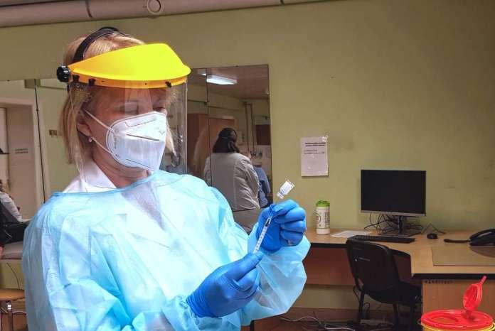 Kobieta przygotowuje szczepionkę do zaaplikowania. Niestety chip do kontrolowania higieny zaszczepionych zablokował gardziołko ampułki.