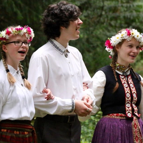 Students wearing folk clothing in the woods at Kursa.