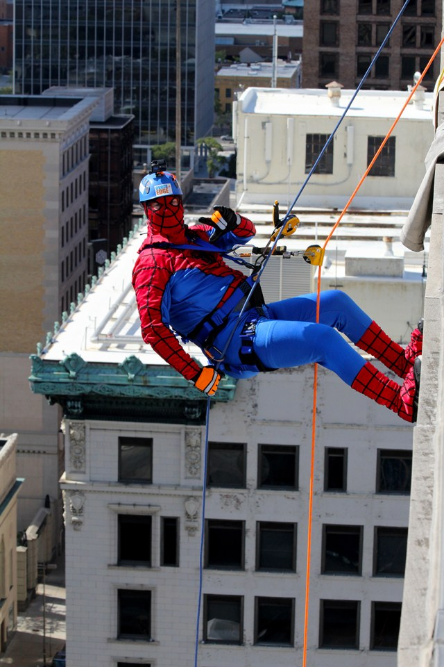 Spiderman rappelling down the building