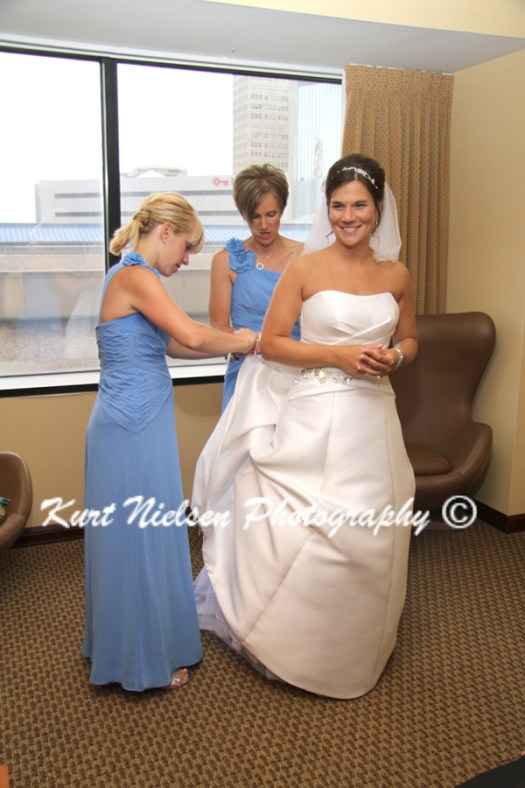 helping the bride bustle her dress