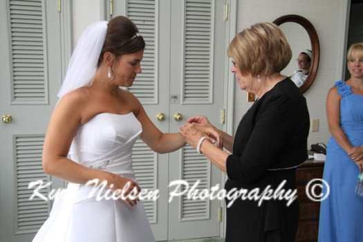 mom helping bride with bracelet