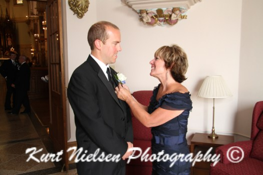 mom pinning on groom's boutonniere