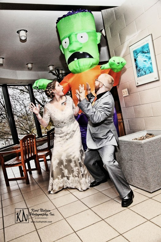 fun halloween photo of bride and groom being chased by blow up frankenstein