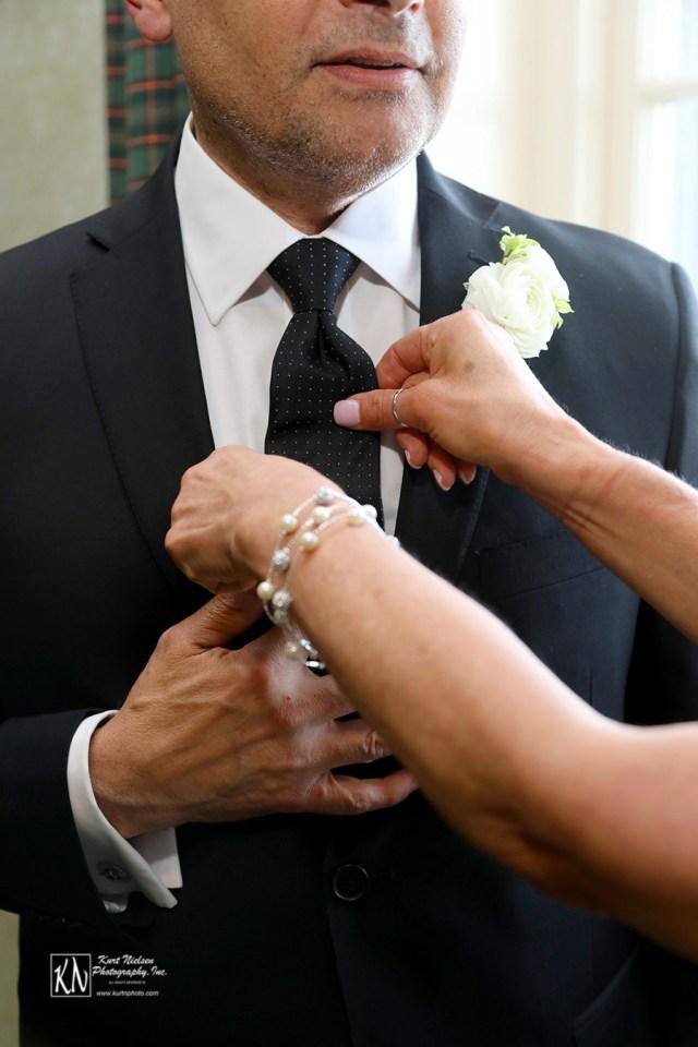 straightening the groom's tie