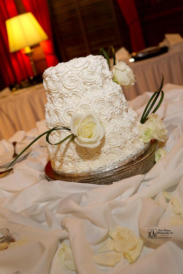 white wedding cake with icing roses