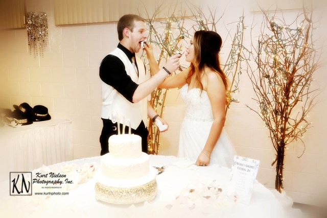 bride and groom serving the wedding cake to each other