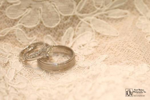 wedding and engagement rings on the brides lace gown