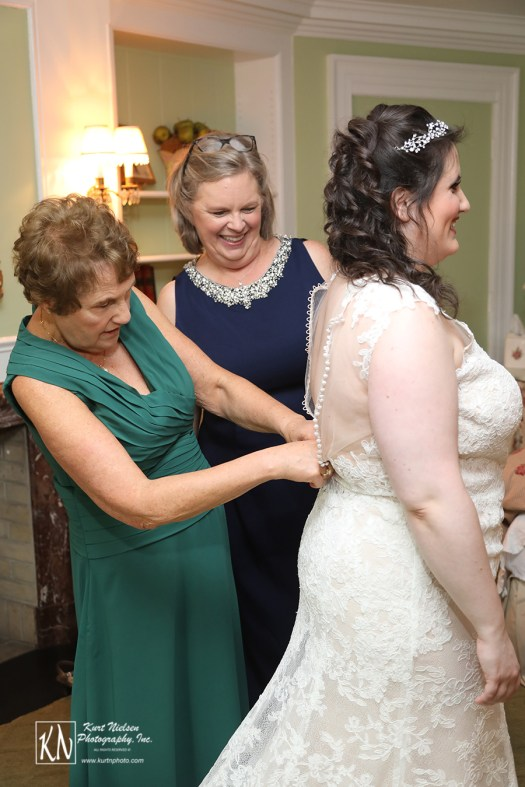 the mom buttoning up the bride's dress