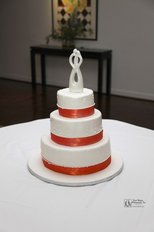 simple wedding cake with orange ribbon