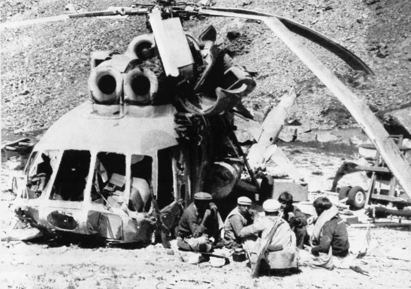 Le mythe écorné: des moudjahidines afghans déjeunent près d'un hélicoptère soviétique Mi-8 abattu.
