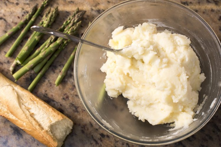 Overhead view of mashed potatoes in a glass bowl with serving spoon in it beside asparagus and a french baguette