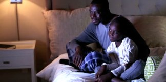 father and son watching tv photo via gettyimages.com