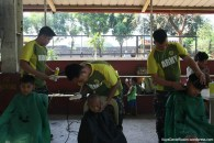 Volunteer barbers from the Armed Forces and Encarnation's Salon give children of Brgy. Balon-bato a summer look hairstyle during UNTV's People's Day.