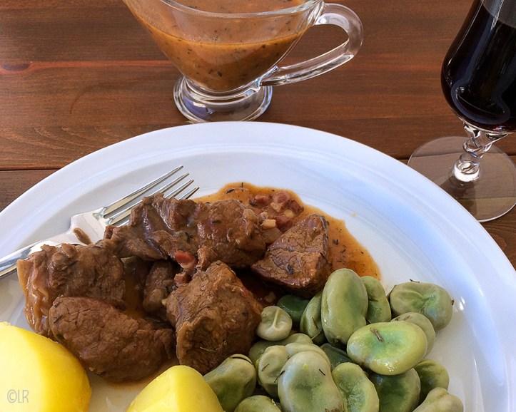 Bord met botermalse stukjes stoofvlees met tuinboontjes en aardappels. Ernaast een schaaltje jus en een glas rode wijn.