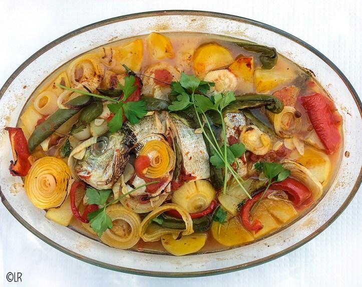 Schotel met dorade in een jus van visbouillon en wijn met ui, aardappel, rode en groene paprika