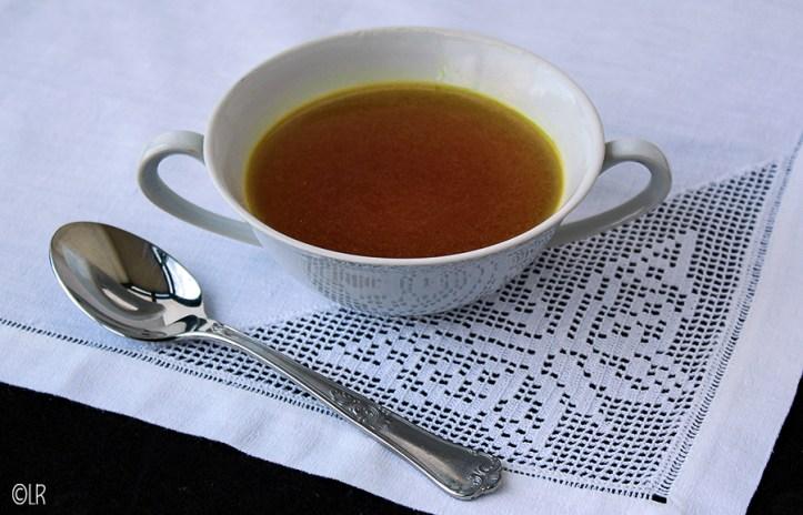 Kopje geurige eigengemaakte bouillon op een kanten kleedje met een lepel ernaast.