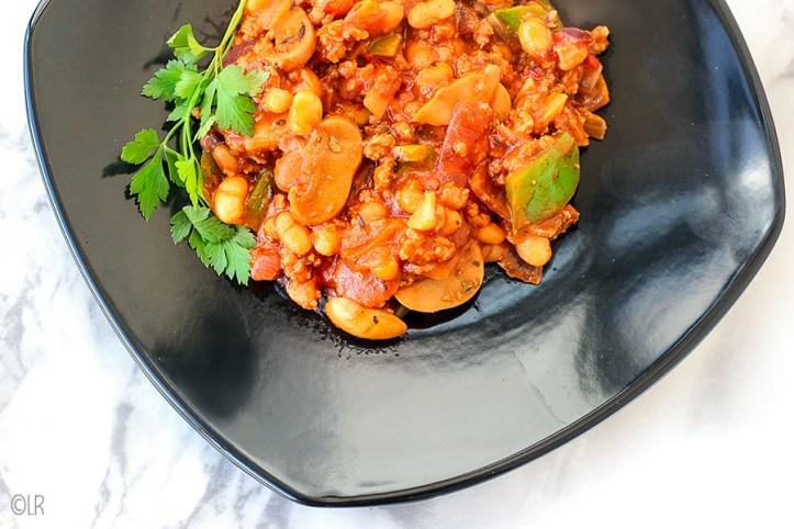 Zwart bordje met een verrassend lekkere chili con carne schotel van witte bonen in tomatensaus,