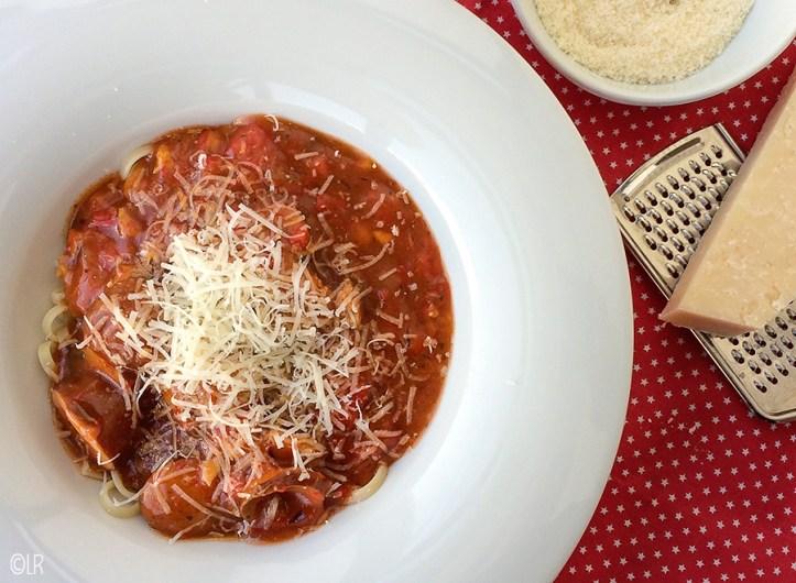Bord spaghetti met saus en geraspte Parmezaanse kaas. Er naast een stuk Parmezaanse kaas op een rasp en geraspte kaas in een schaaltje.