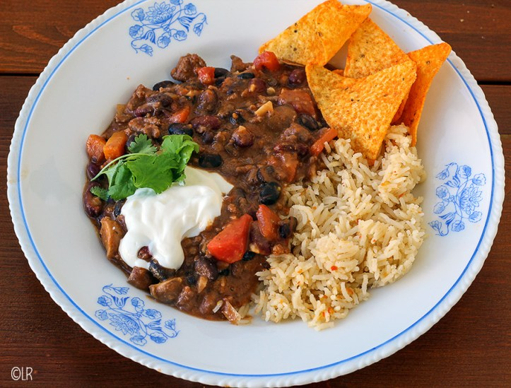 Mooi wit met blauw bord met Chili con carne geserveerd met een toefje zure room, wat koriander, rijst een paar taco's