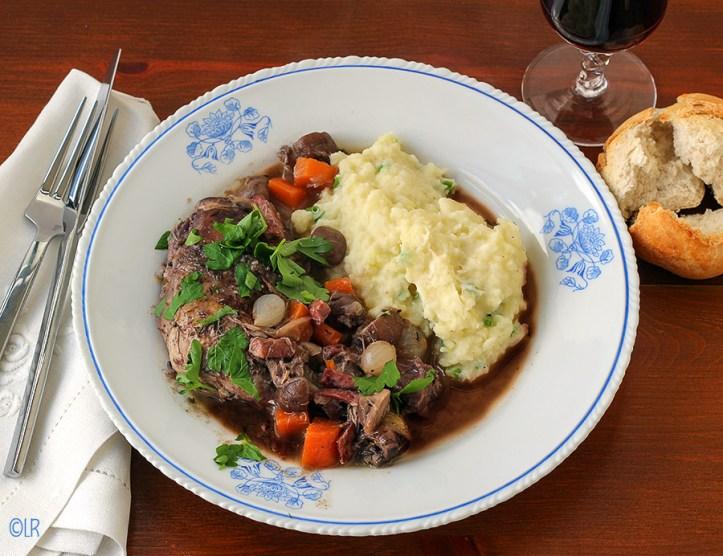 Bord met in wijn gestoofde kippenbout met lekkere aardappelpuree erbij. Een stukje brood voor de jus en een glaasje wijn maken het compleet.