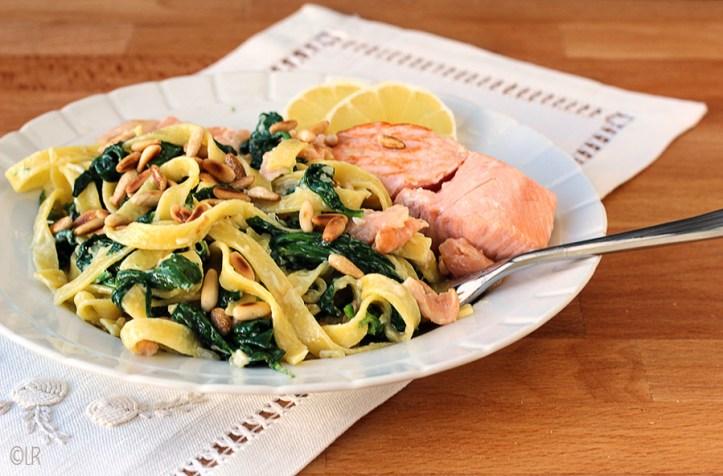 Bordje met een fraaie compositie van gebakken zalm met spinazie-tagliatelle en pijnboompitjes.
