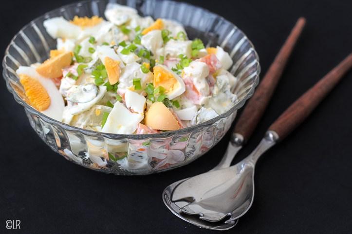 Kleurrijke salade van meiknol, wortel, augurk en hardgekookte eieren.