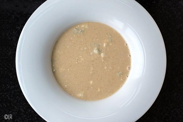 Bord met romige witlofsoep met stukjes blauwe kaas.