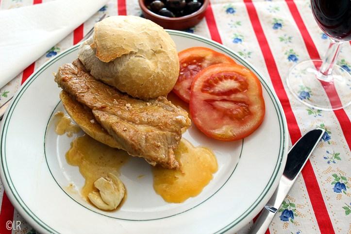 Dun lapje varkensvlees op een broodje met twee schijfjes tomaat - een gezonde lunch.