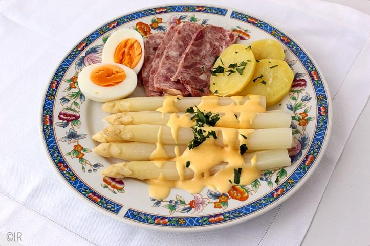 Bordje asperges, met ei, ham en aardappelschijfjes overgoten met hollandaisesaus.
