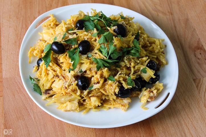 Op een schotel geserveerd de zoute vis met frietsticks en ei gegarneerd met olijven en peterselie.