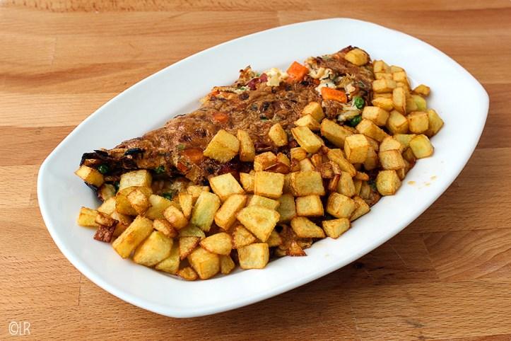 Schotel met rijkgevulde omelet met gefrituurde aardappeltjes.