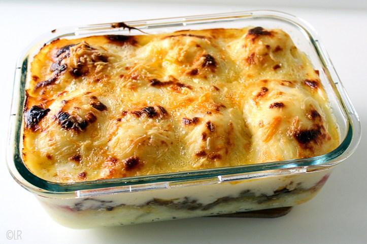 Ovenschotel van gehakt, aardappelpuree en bloemkool met een kaassaus.