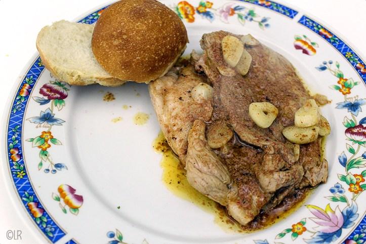 Heerlijk Portugees gemarineerd lapje varkensvlees in een saus met veel knoflook met een broodje.