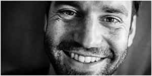 Lächelnde Nahaufnahme eines schwarzhaarigen Mannes mit 3-Tagebart in Schwarz/Weiß