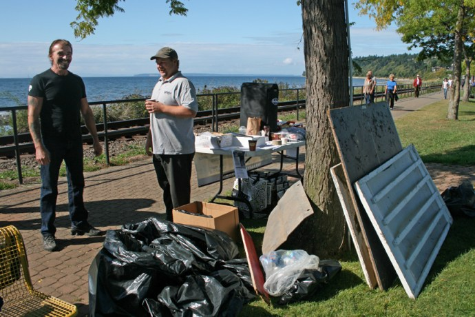 James Casineau (right) a Kary Movers and Jim Abbott (left), a local musician, guard the event table and accumulated garbage in White Rock on Saturday September21, 2013.
