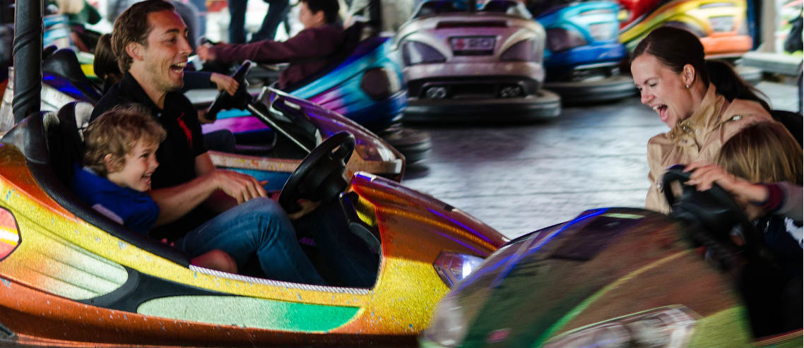 parents ride bumper cars with their kids and collide with hilarious force, outlining the need to think about family car insurance before it's too late