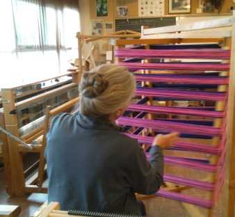 A weaver makes a warp in the Guild studio.