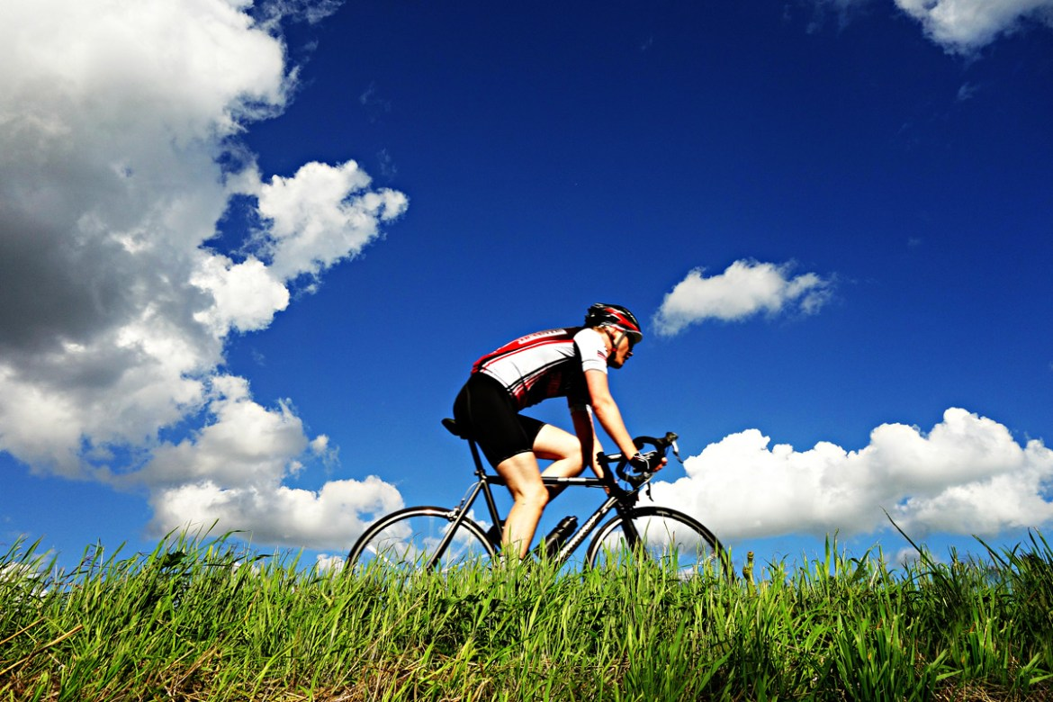 man cycling against beautiful sky