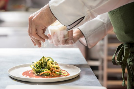 Chef Michael Luboff puts the finishing touches on a dish he created using noodles made from zuchinnis that are cut in a special way to spiralize them into long, pasta-like shapes.