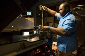 In the final stages of 'threading' the 70mm film, Dwayne Blyden passes the filmstrip behind the lens of the IMAX projector at the Maritime Aquarium in Norwalk, Conn. on May 4, 2016.