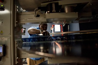 Projectionist Dwayne Blyden fixes the 'leader' - the beginning of the filmstip - to the tray that will pull the rest of the movie across the projector's lens. Norwalk, Conn on May 4, 2016.