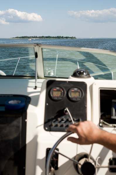 The helm of Clyde Ripka's boat heading to Sheffield Island. In the distance, Shea Island, a neighbor to Sheffield. Norwalk, Conn on June 30, 2016.