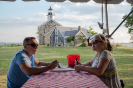 Customers of the Ripka's clambake, Patryk and Grace Zelechowski of Norwalk, Conn., dine beneath Sheffield Island Light on June 30, 2016.