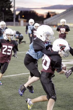 (Left) A Laramie youth football player attempt to break a tackle to reach the end-zone. Photo courtesy of boomphotos.com