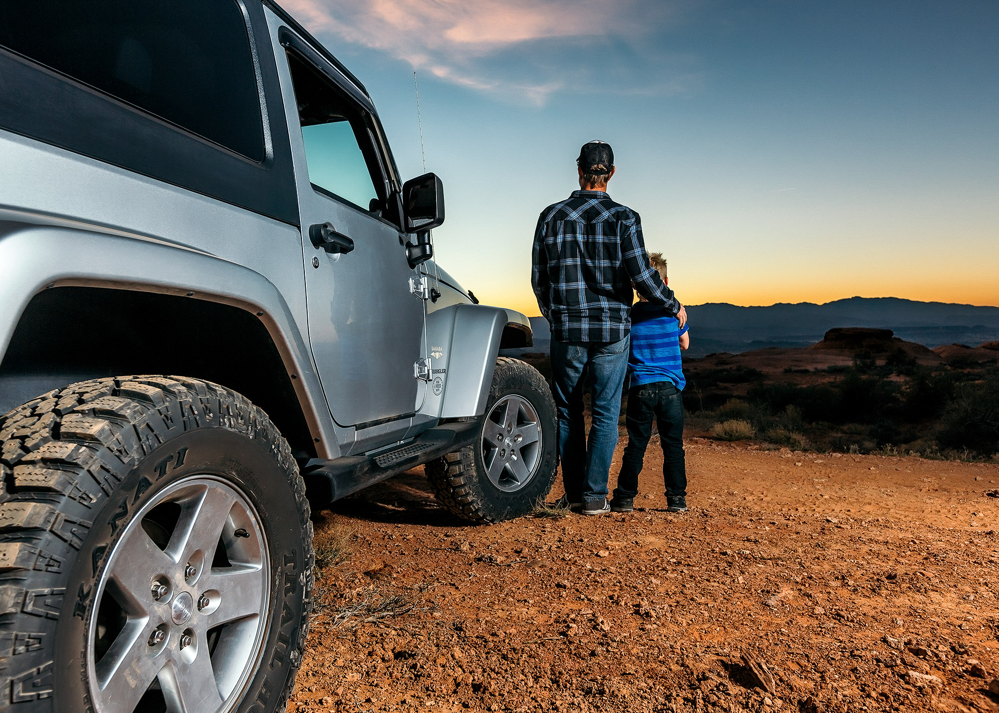 father and son watch sunset by jeep