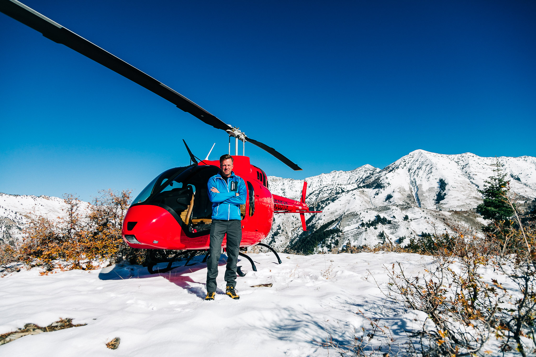 Man standing in front of bell 500 helicopter