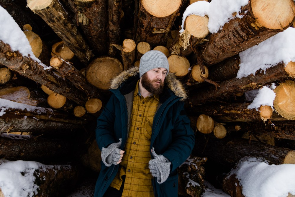 JCrew Nordic Down Parka in front of logs