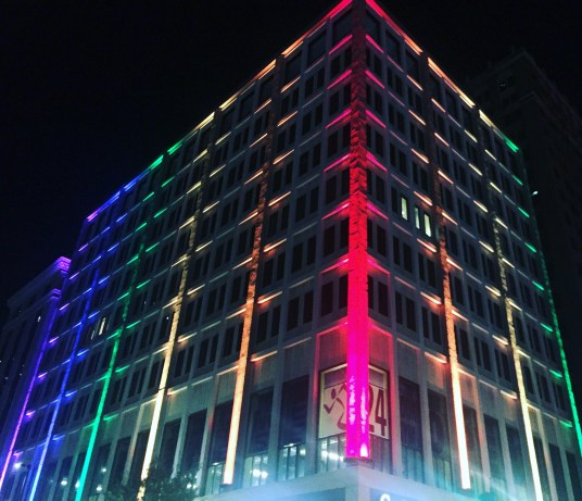 A building downtown lit up in rainbow colors