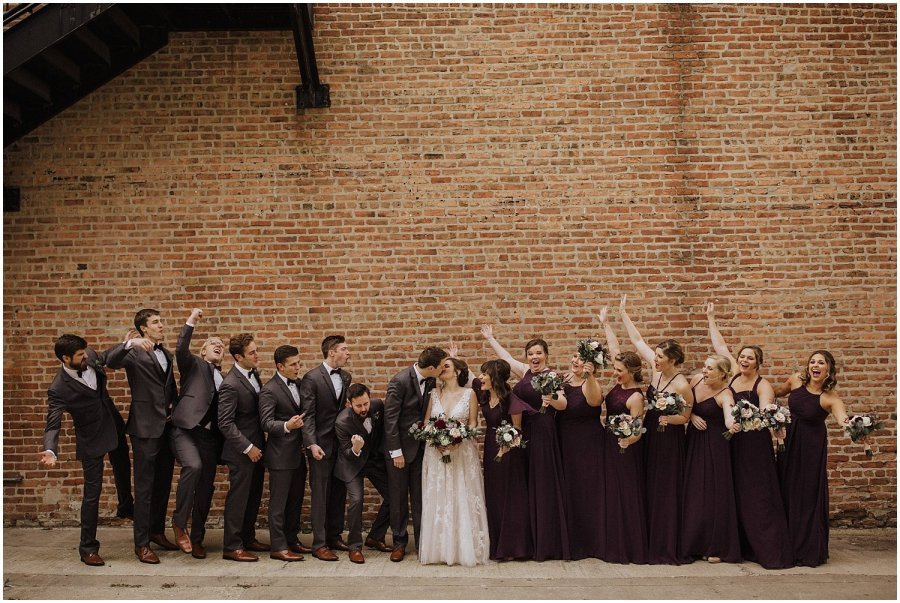 bridal party cheering as couple kiss